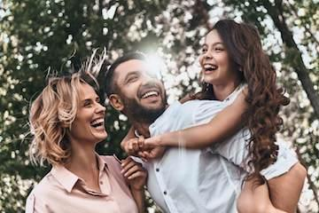 family of three daughter on fathers back smiling