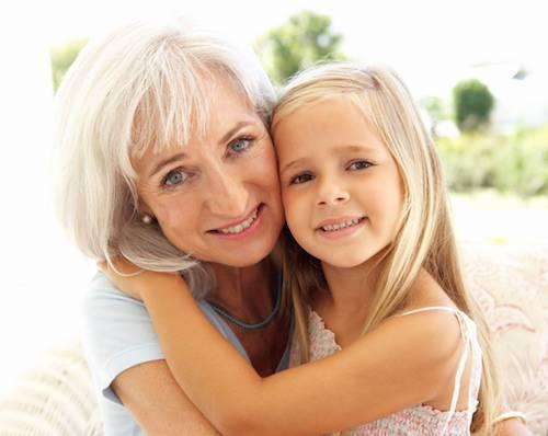older woman with white hair and blue eyes holding a young blonde girl with brown hair